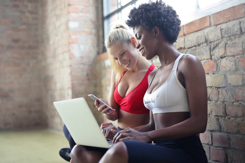Women in workout clothes in front of laptop